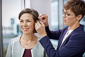 Audiologist fitting a female patient with a hearing aid