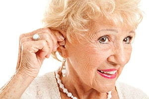 older woman cups ear around hand in order to hear better