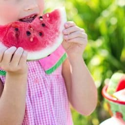 child eating a watermelon outside