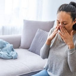 Woman with sinus pressure holding hands to her face.