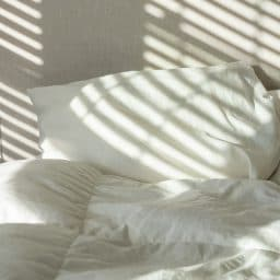 A pile of white pillows on a bed.